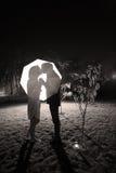Paare, die unter dem Regenschirm küssen Stockfoto