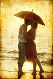 Paare, die unter Regenschirm küssen Stockfoto
