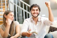 Paare, die Videospiele auf der Couch spielen Stockbild