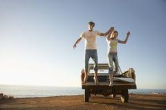Paare, die von der Rückseite von Van Parked By Ocean springen Lizenzfreies Stockbild