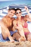 Paare, die von Sun unter Strand-Regenschirm schützen Stockfoto