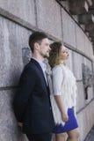 Paare, die vor dem hintergrund einer Wand aufwerfen Stockfotografie
