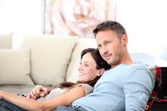 Paare, die vor Fernsehapparat sich entspannen Lizenzfreies Stockfoto
