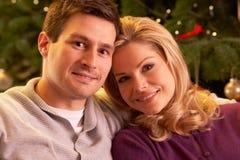 Paare, die vor Weihnachtsbaum sich entspannen Lizenzfreies Stockfoto