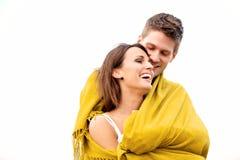 Paare, die während Sie in der Decke umarmen, eingewickelt werden Stockfotografie