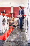 Paare, die Waschmaschine im Grossmarkt wählen Stockbild