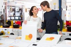 Paare, die Waschmaschine wählen Stockfoto