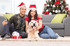 Paare, die Weihnachten zusammen mit ihrem Hund feiern Stockbild