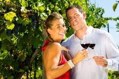 Paare, die am Weinberg und an trinkendem Wein stehen Lizenzfreie Stockfotos