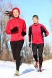Paare, die in Winterschnee laufen Stockfotografie