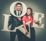 Paare, die Wort LIEBE halten Stockbilder