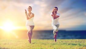 Paare, die Yoga Adler draußen aufwerfen lassen Stockfotografie