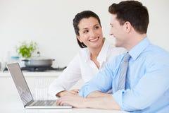 Paare, die zu Hause on-line-Kauf abschließen Stockbilder
