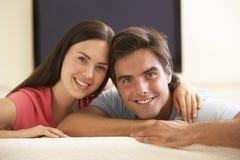 Paare, die zu Hause mit großem Bildschirm fernsehen Stockfoto