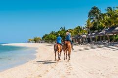 Paare, die zu Pferd entlang das Meer reiten Lizenzfreie Stockfotografie