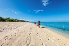 Paare, die zu Pferd entlang das Meer reiten Lizenzfreie Stockbilder