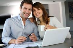 Paare, die an zukünftigem Hausplan arbeiten Lizenzfreie Stockfotos