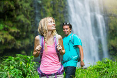 Paare, die zum Wasserfall wandern Lizenzfreie Stockfotografie