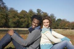 Paare, die zurück zu Rückseite auf dem Gebiet sitzen Stockfotografie