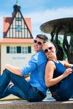 Paare, die zurück zu Rückseite nahe dem Brunnen sitzen lizenzfreies stockbild