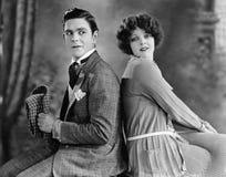 Paare, die zurück zu hinterem sitzen und (alle dargestellten Personen, flirten, sind nicht längeres lebendes und kein Zustand exi Lizenzfreie Stockfotos