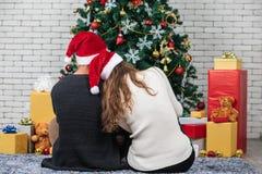 Paare, die zusammen auf Boden vor großem verziertem Chris sitzen lizenzfreie stockfotos