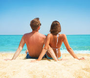 Paare, die zusammen auf dem Strand sitzen Lizenzfreie Stockfotos