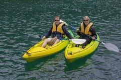 Paare, die zusammen auf einem See Kayak fahren Lizenzfreies Stockfoto