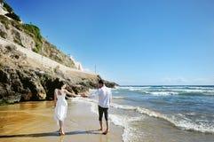 Paare, die zusammen auf Händchenhalten des Strandes gehen Stockfotografie