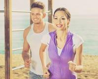Paare, die zusammen auf Strand durch Ozean laufen Stockfoto