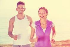Paare, die zusammen auf Strand durch Ozean laufen Lizenzfreie Stockfotos