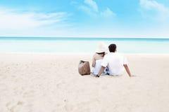 Paare, die zusammen auf Strand sitzen Lizenzfreies Stockfoto