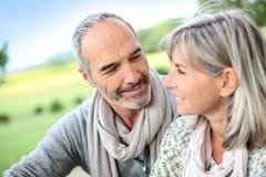 Paare, die zusammen in der Landschaft sitzen Lizenzfreies Stockbild