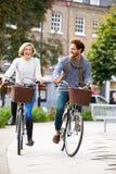 Paare, die zusammen durch städtischen Park radfahren Stockfotos