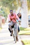 Paare, die zusammen entlang Vorstadtstraße radfahren Lizenzfreie Stockfotos