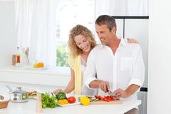 Paare, die zusammen in ihrer Küche kochen Stockbilder