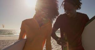 Paare, die zusammen mit Surfbrett auf dem Strand 4k gehen stock footage