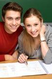 Paare, die zusammen an Schulearbeit arbeiten Lizenzfreie Stockfotos