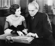 Paare, die zusammen sitzen und ein Buch mit einem besorgten Gesichtsausdruck betrachten (alle dargestellten Personen sind nicht l stockbild