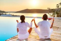 Paare, die zusammen am Sonnenaufgang meditieren Stockbild