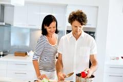 Paare, die zusammen zu Hause kochen Lizenzfreie Stockfotos