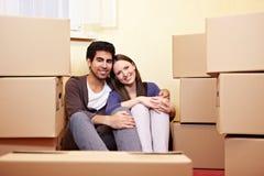 Paare, die zwischen Verpackung sitzen Lizenzfreie Stockfotos
