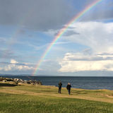 Paare durch Seeaufpassenden Regenbogen Stockbild