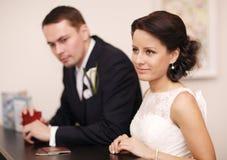 Paare an einem Aufnahmeschreibtisch mit ihren Pässen Stockfotografie