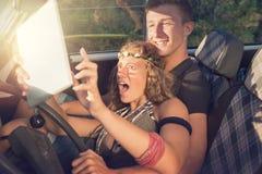 Paare in einem Auto bei Sonnenuntergang Stockbilder