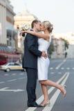 Paare in einem Kuss auf der Straße Jungvermählten, die auf dem Trennstreifen küssen Hochzeitsthema Stockbilder