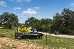 Paare in einem Motorrad, das durch einen LKW mit einem Zeichen für ein Musikereignis in Luckenback, Texas überschreitet Stockbilder