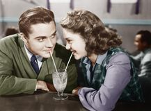 Paare in einem Restaurant, das einander betrachtet und einen Milchshake mit zwei Strohen teilt (alle dargestellten Personen sind  Stockbild