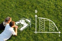 Paare in einer Wiesenplanungshypothek für ein Haus Stockfoto