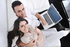 Paare entspannen sich und arbeiten an Laptop-Computer zu Hause Lizenzfreie Stockfotografie
